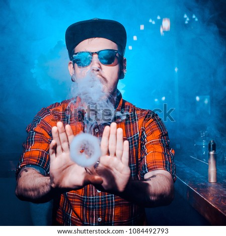 Punk hipster man is smoking a mechanical vape device. Toned image. The concept of popularization of vaping. Vaping man in sunglasses lets out a lot of rings of steam or smoke nice try #1084492793