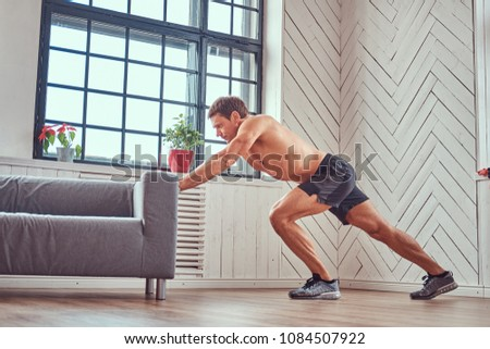 Handsome shirtless muscular male does exercise leaning on a sofa at home. #1084507922