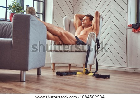 Handsome shirtless muscular male lying on the chair, resting after a hard workout at home. #1084509584