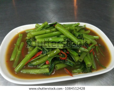 Morning glory / Stir Fried Swamp Cabbage on a white plate placed on a stainless steel table.Quick-fried water spinach seasoned with chili and soy sauce #1084512428