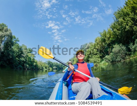 Active happy family. Girl with her mother having fun together enjoying adventurous experience kayaking on the river on a sunny day during summer vacation #1084539491