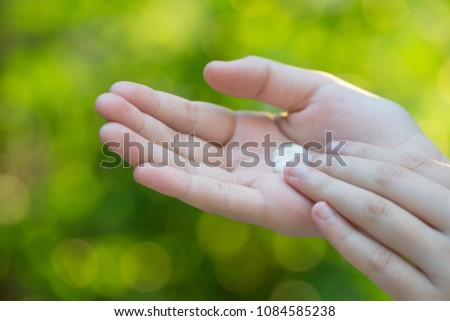 Closeup of female hands applying cream on her arm. Make up, healthy skin, beauty shot, cute asian woman concept #1084585238