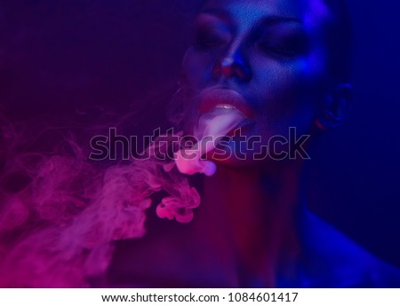 Halloween Party, Nightlife. Beautiful Sexy Young Woman with glamorous mystical makeup vaping in Nightclub neon, exhaling smoke. Girl smoking vaporizer in Club. Blue mystic smoke