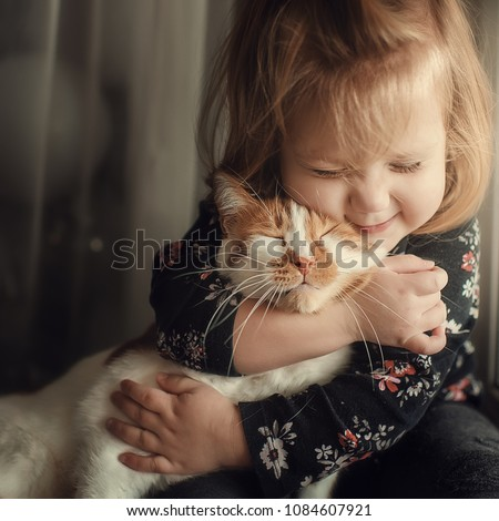 Portrait of a small cute child with a bald head that embraces with tenderness and love a red cat and smiles with happiness #1084607921