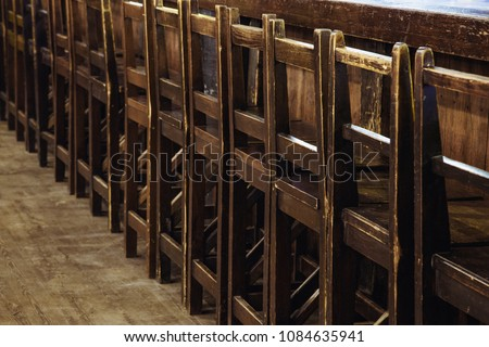 empty wooden chairs in the restaurant stand in a row along the bar counter #1084635941