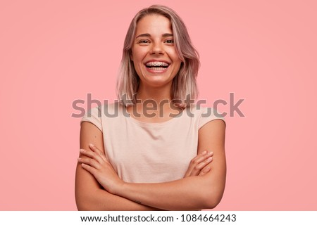 People, happiness and facial expressions concept. Pretty young woman with broad shining smile, keeps hands crossed, being in high spirit, wears braces on teeth, poses alone against pink background #1084664243