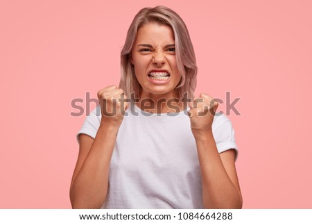 Aggressive female looks angrily and irritated, keeps teeth pressed and clenches fists, has furious expression, gestures with annoyance, has quarrel with enemy, poses against pink background. #1084664288