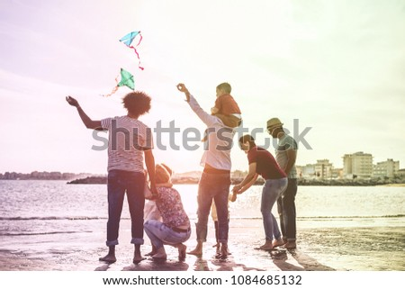 Happy families flying with kite and having fun on the beach - Parents playing with children outdoor - Love and holidays concept - Main focus on left man - Radial purple and green filters editing #1084685132