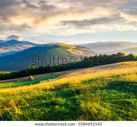 beautiful rural scenery in mountains at sunrise. haystack on the field behind the fence. outdated agriculture approach concept #1084692542