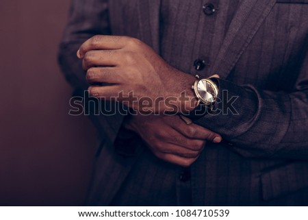 Important accessory. Close up of a watch of a smart confident handsome businessman being on its wrist #1084710539