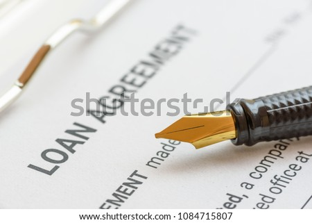 Business loan agreement or legal document concept : Fountain pen on a loan agreement paper form. Loan agreement is a contract between a borrower and a lender, a compilation of various mutual promises. #1084715807
