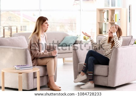 Young female psychologist working with teenage girl in office #1084728233