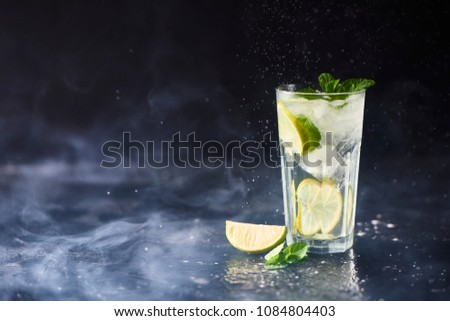 Mojito cocktail with lime and mint in highball glass with smoke on dark stone background. #1084804403