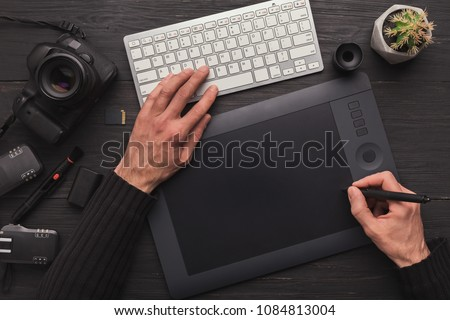 Top view on workplace of photographer. Creative designer hands working with computer keyboard and graphic tablet, photographic equipment on table #1084813004