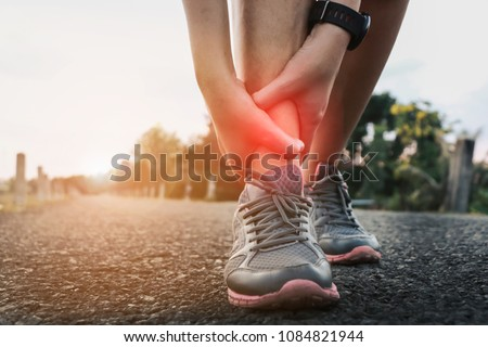 Ankle twist sprain accident in sport exercise running jogging.sprain or cramp Overtrained injured person when training exercising or running outdoors. #1084821944