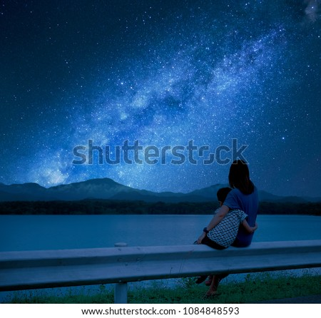 Silhouette mother and child sitting together to hold the view outside the lake. Enjoy the view of the Milky Way on a romantic night. #1084848593