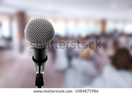 Microphone on boom stand ready for the meeting ,blurred background group of people sitting around table. Microphone on stage in conference hall. Let's talk