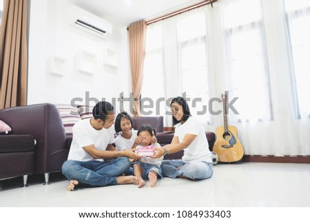 Happy asian family little cute girl with closed eyes give a gift, Sitting room on a floor at home #1084933403