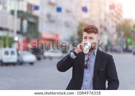 Portrait of a beautiful business man drinking coffee in the background of a blurred urban landscape. #1084976318