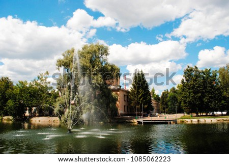 View of a beautiful lake with fountaing in a green blooming park #1085062223