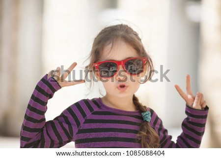 A little girl of 6 years in sunglasses is happy and gesticulates with her hands and fingers #1085088404