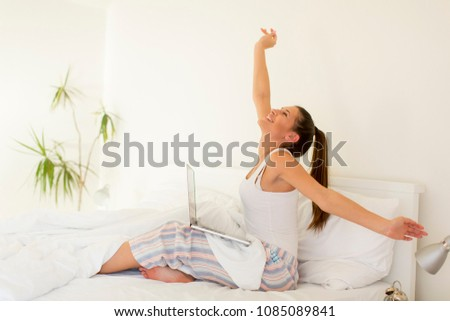 Smiling woman catching up on her social media as she relaxes in bed with a laptop computer on a lazy day #1085089841