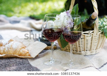 Picnic with delicious wine in basket and glass with red wine and croissant #1085137436
