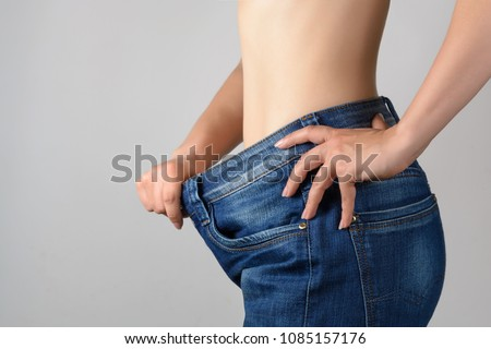 Torso of a young slim woman in big jeans. Results after training and diet. #1085157176
