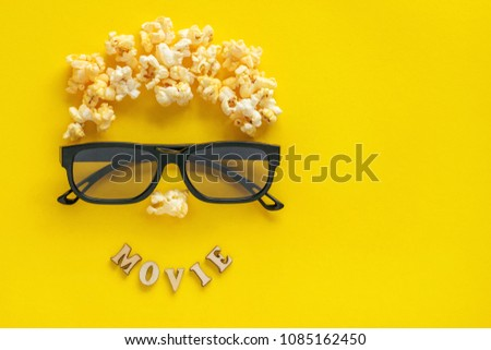 "Abstract image of viewer, 3D glasses and popcorn,  text  ""movie"" on yellow background. Still life, top view, flat lay. Concept cinema and entertainment"