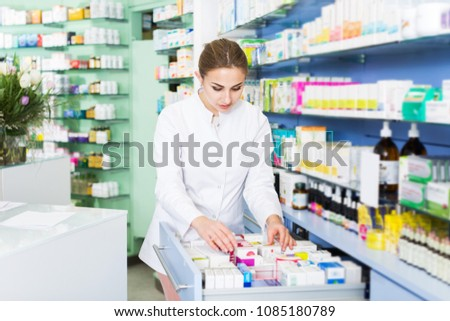 Woman specialist is attentively looking medicines in lockers in pharmacy #1085180789