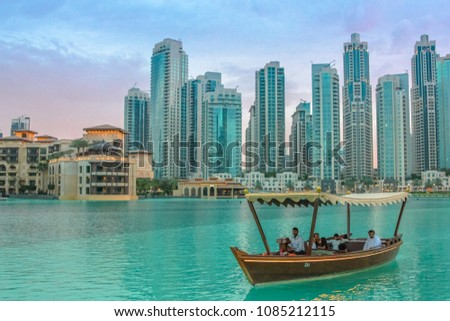 Dubai, UAE - May 1, 2013: tourists take a boat ride near Dubai fountain show area, Dubai Mall and Burj Khalifa, in front of Souk Al Bahar. On background, the skyscrapers of Old Town Island at sunset. #1085212115