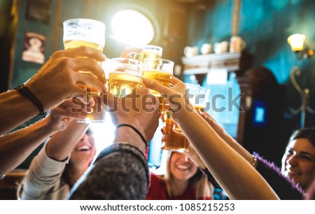 Group of happy friends drinking and toasting beer at brewery bar restaurant - Friendship concept with young people having fun together at cool vintage pub - Focus on middle pint glass - High iso image Royalty-Free Stock Photo #1085215253