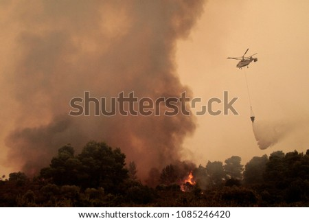A Helicopter drops water during a forest fire on Ouranoupoli, Greece on Aug. 9, 2012 #1085246420