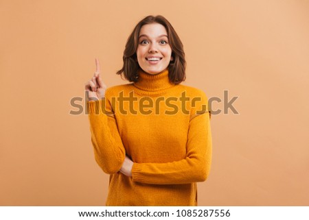 Portrait of an excited young woman in sweater pointing finger up at copy space over beige background #1085287556