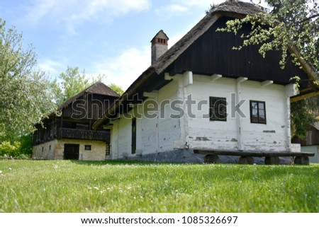 Small old white house with straw roof #1085326697
