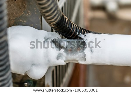 ac cooling air pipes covered by snow or frozen because of super performance of heavy duty central air conditioning system on the roof top in hot summer days   #1085353301