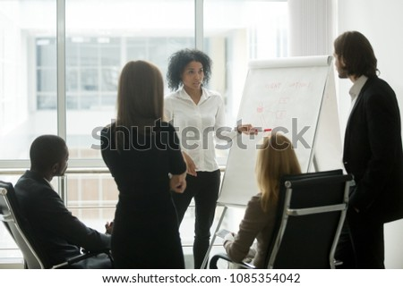 Serious african female leader or coach gives presentation of new marketing plan at sales team meeting, black employee explains colleagues new client management strategy idea at group office training #1085354042