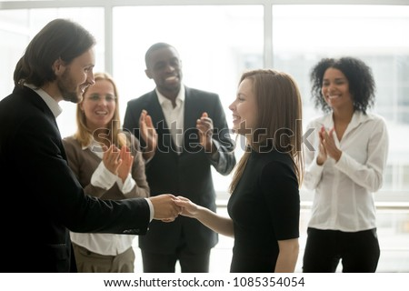 Smiling ceo promoting rewarding handshaking motivating female worker congratulating with promotion or success showing respect while team applauding, appreciation and employee recognition concept #1085354054