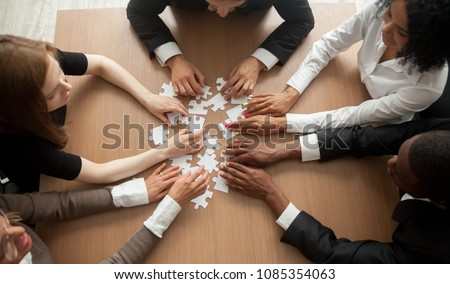 Diverse team people assembling jigsaw puzzle, multiracial group of black and white colleagues engaging in successful teamwork finding business solution, corporate unity teambuilding concept, top view #1085354063