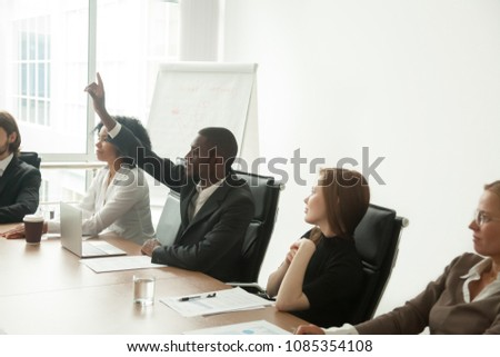African businessman in suit raising hand at corporate diverse group meeting, black employee voting as volunteer asking question at business training sitting at conference table with multiracial team #1085354108