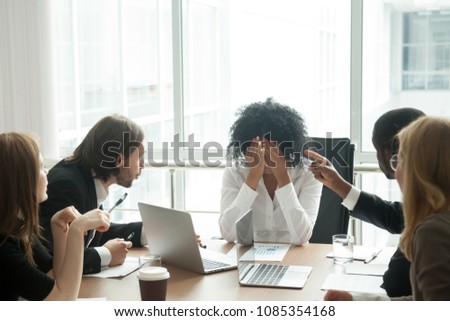Rude diverse colleagues humiliating offending stressed upset young african woman leader suffering from gender racial discrimination during meeting or feeling exhausted tired of responsibility at work #1085354168