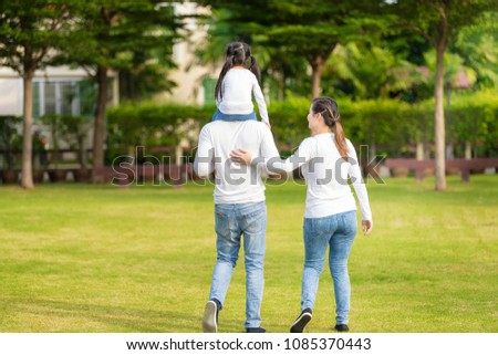 Cute Asian girl on neck parents big happy laughing and run around together.Happy family piggybacking adorable little daughter is smiling. #1085370443