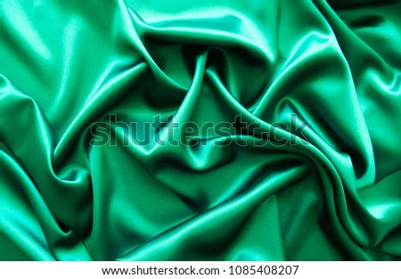 Beautiful smooth elegant wavy green satin silk luxury cloth fabric texture, abstract background design. Card or banner.