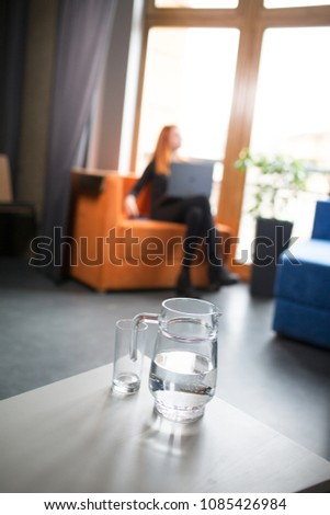 Young red hair woman working in empty meeting room. One busines lady working with lap top in conference room. Bottle of water. #1085426984