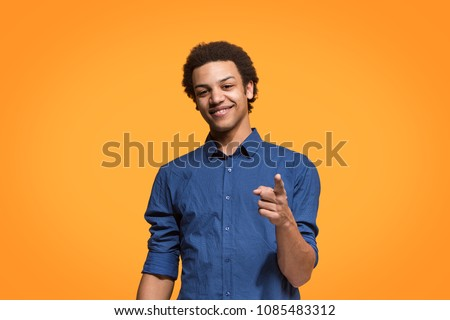 I choose you and order. The smiling business man point you, want you, half length closeup portrait on orange studio background. The human emotions, facial expression concept. Front view. Trendy colors #1085483312
