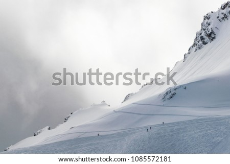 Distant skiers on snowy slope with sharp ridge behind and cloudy sky #1085572181