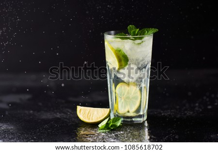Mojito cocktail with lime and mint in highball glass on dark stone background. #1085618702