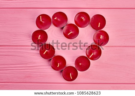 Red heart from candles, top view. Small red candles arranged in heart shape on pink wooden background with copy space. Love and romance concept. #1085628623