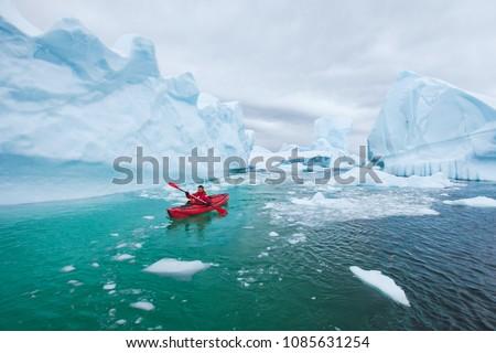 man paddling on kayak between ice in Antractica in Iceberg Graveyard, extreme winter kayaking, polar adventure near Pleneau island #1085631254