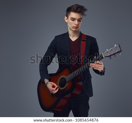 Handsome young musician with stylish hair in elegant clothes, playing on an acoustic guitar. #1085654876